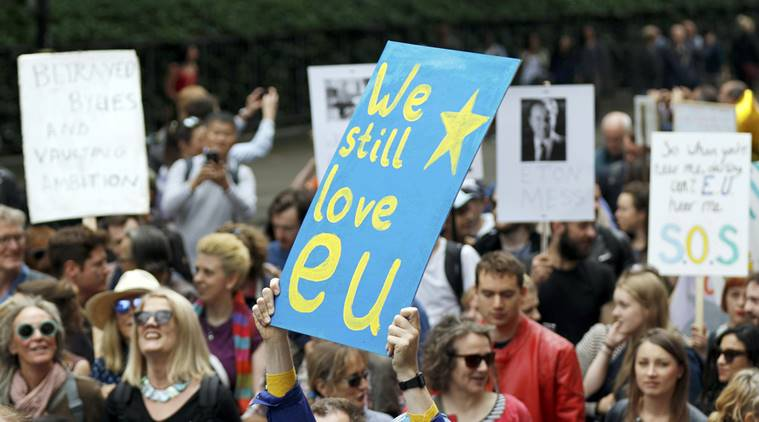 People hold banners during a demonstration against Britain's decision in BREXIT