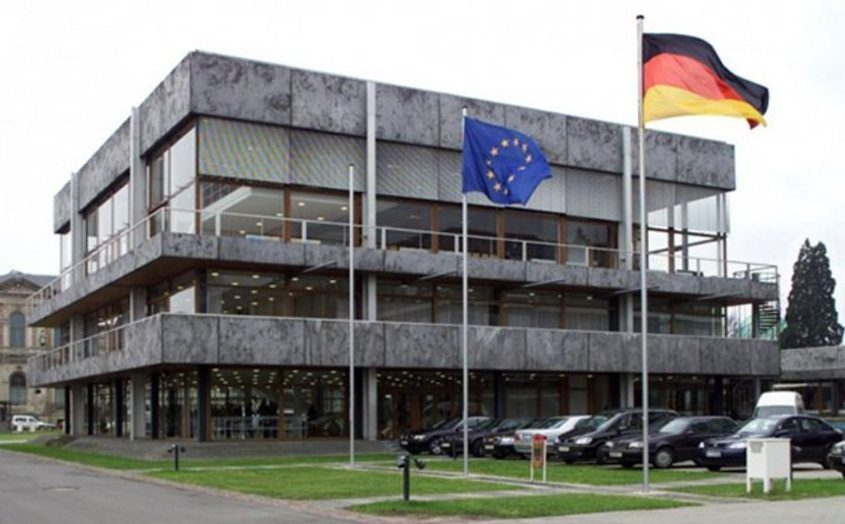German Federal Constitutional Court with Euro and German flying flags with car parking