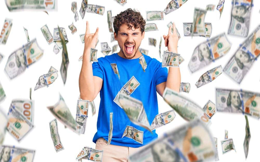 A young curly man throwing money after making greedy forex profits