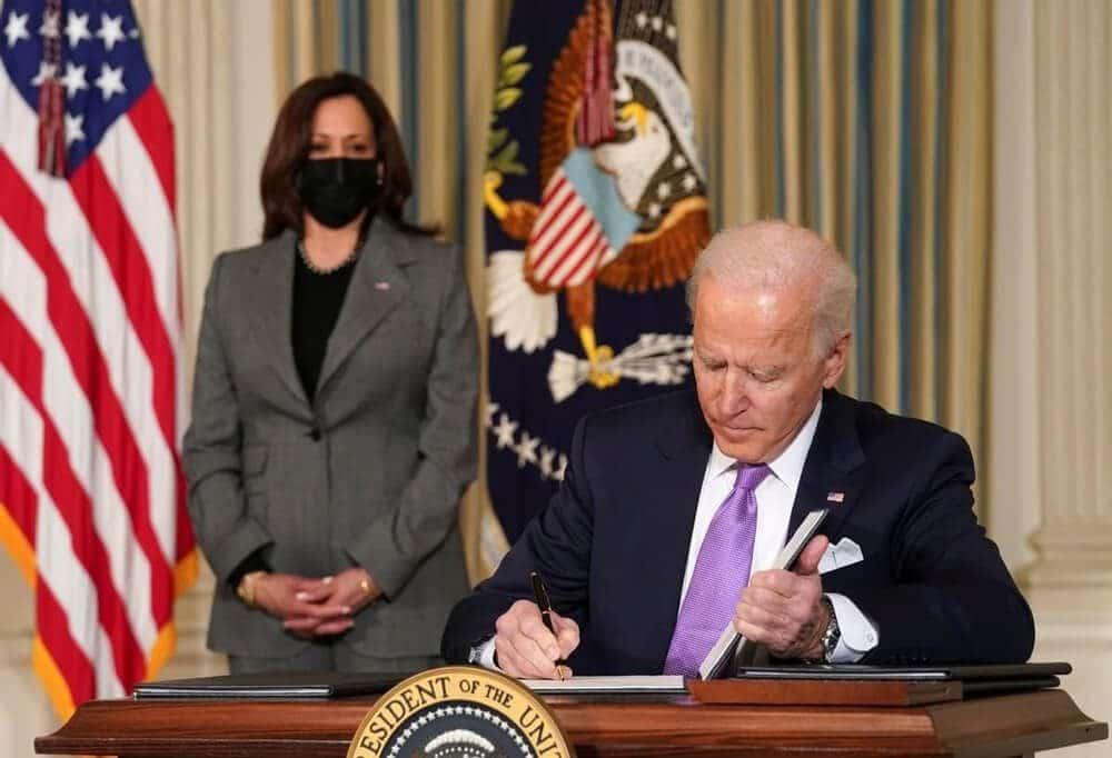 US Presideng Joe Biden signing the deal and vice president kamala behind