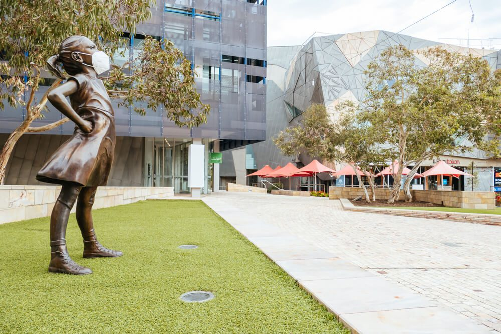 Australia Lockdown Federation Square and a masked statue of Fearless Girl in Melbourne is quiet and empty during the Coronavirus pandemic