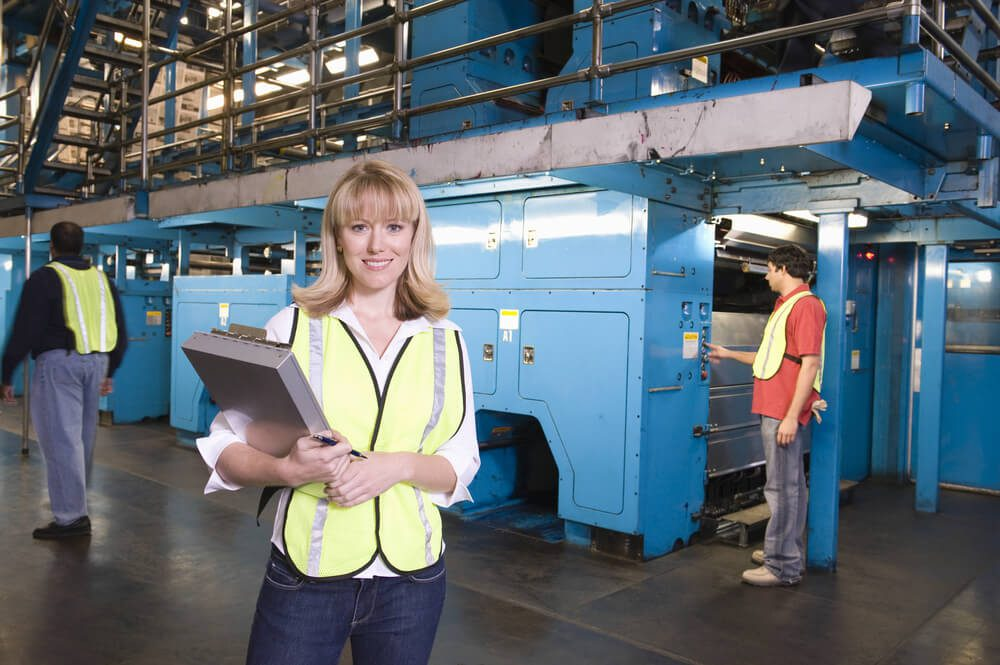 US Manufacturing data woman holding clipboard with operators in background at the factory
