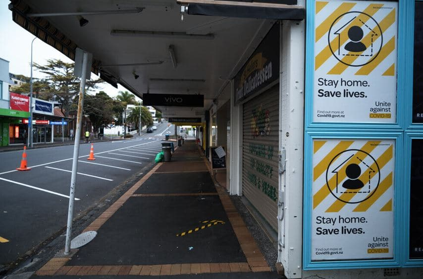 Stay home save lives posters on a billboard and closed shops and empty deserted streets during the coronavirus covid 19 lockdown